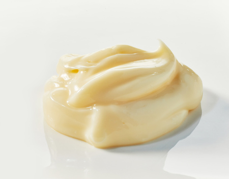 Low profile twist of gourmet mayonnaise with reflection on white in a close up side view for food styling concepts