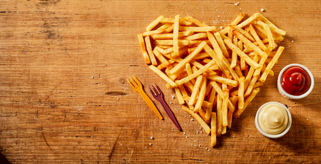 Herzförmiges Servieren oder gebratene Kartoffelchips auf rustikalem Holz mit Schüsseln mit Senf- und Mayonnaisemischung und Tomatensauce von oben gesehen mit Kopierraum