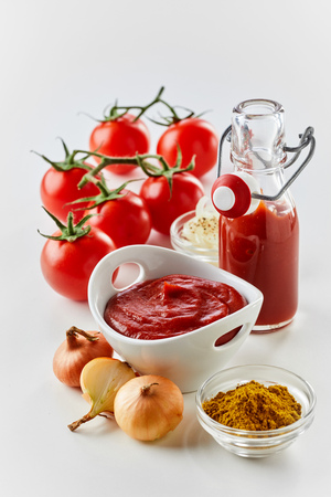 Spices and ingredients for fresh homemade ketchup or tomato sauce with vine tomatoes, puree, onion and ground spice on a white background