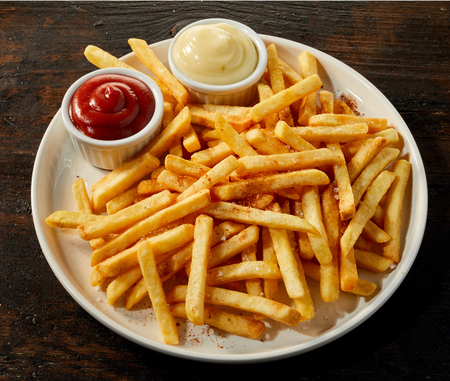 Large plateful of crispy French fries with tomato sauce and mayonnaise dips in bowls viewed high angle on wood