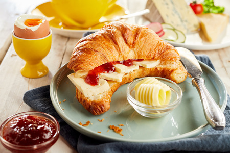 Croissant filled with cheese and ketchup, served on ceramic plate with butter curls and soft-boiled egg. Restaurant table close-up view