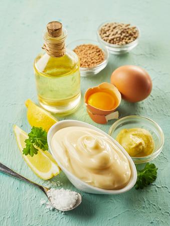 Schüssel mit würziger hausgemachter Mayonnaise mit frischer Zitrone, Salz, Öl, Gewürzen und Eiern auf einem strukturierten hellgrünen Holztisch mit hohem Winkel Standard-Bild