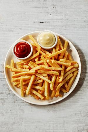 Teller mit Pommes-Frites-Kartoffeln serviert mit Ketchup und Mayonnaise-Saucen in kleinen Schüsseln, von oben gesehen isoliert auf grauem Holzhintergrund