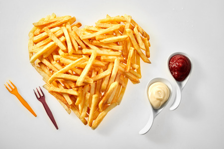 Herzförmige Anordnung von Pommes frites mit Tomatensauce und Mayonnaise in Keramiklöffeln und Plastikgabeln auf weißem Hintergrund