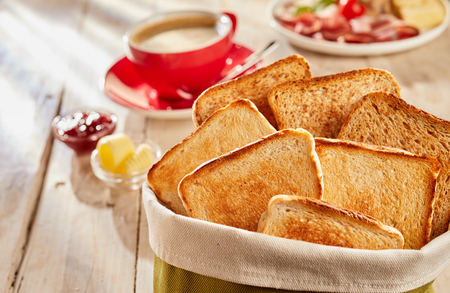 Fresh crunchy toasts bread slices served in fabric bag, with cup of coffee and butter for breakfast 写真素材