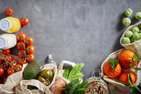 Fresh organic vegetables and other groceries in fabric eco-friendly bags in kitchen copy space layout with grey background