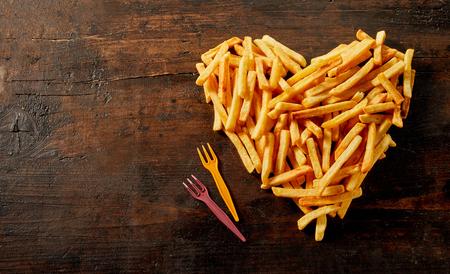 Herzförmiges Stillleben mit Pommes Frites von oben auf Vintage-Holz mit Kopierraum und Plastikgabeln Standard-Bild