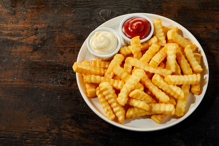 White ceramic plate of rippled french fries served with ketchup and mayonnaise, viewed from above on dark wooden background with copy space