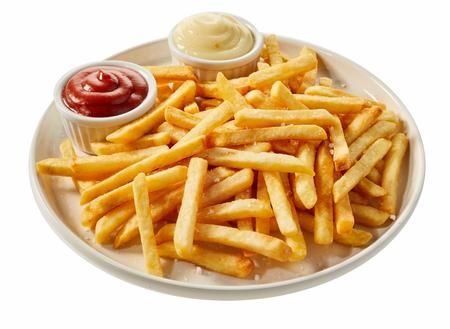 Weißer Keramikteller mit frisch zubereiteten Pommes frites serviert mit Ketchup und Mayonnaise in kleinen Schälchen, in Nahaufnahme betrachtet, einzeln auf weißem Hintergrund