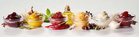 Row of glass bowls with sauces, dressings and marinades with ingredients including aromatic spices, herbs and vegetables on white in a panorama banner