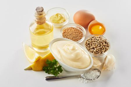 Rezeptzutaten für hausgemachte Gourmet-Mayonnaise mit Eigelb, Öl, Zitrone und Gewürzen in hohem Winkel auf Weiß