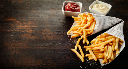 Paper cones with salted French fries spilling out onto dark wood with copy space served with sauces