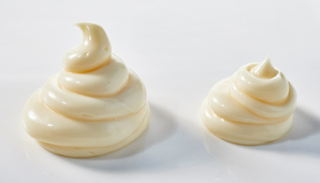 Two twirls of homemade spicy mayonnaise over white for food presentation or styling