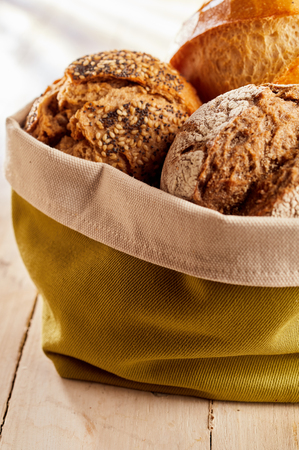Fabric bag with freshly baked buns of brown and white bread