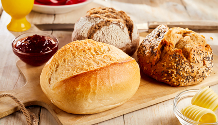 Whole buns of various kinds of fresh baked bread served in restaurant on wooden cutting board, with butter and jam in glass bowls