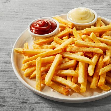 Teller mit goldenen Pommes frites oder Kartoffelchips, serviert mit kleinen Schüsseln Tomatensauce und Mayonnaise Standard-Bild