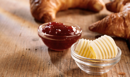 Fresh curls of butter and jam in glass bowls for breakfast with croissants, served on scratched wooden table and viewed in close-up