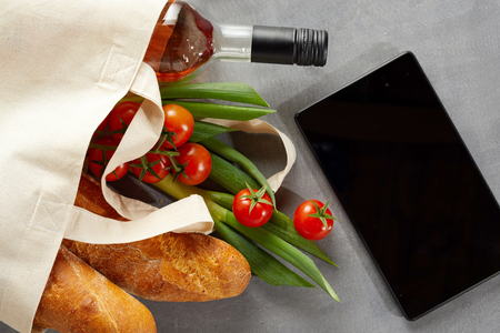 Tablet with fresh groceries and bottle of wine in a reusable textile carrier bag to save on pollution from plastics in the environment Фото со стока