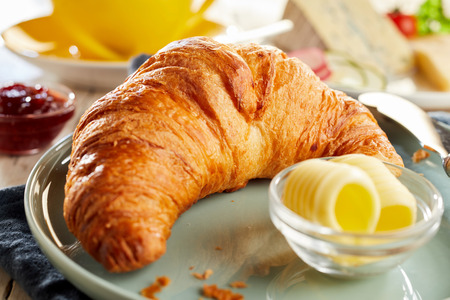 Whole fresh baked flaky croissant served with butter curls. Close-up view Banco de Imagens