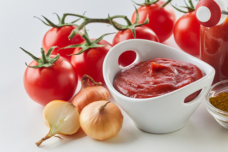 Fresh homemade tomato sauce in a bowl surrounded with ingredients