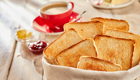 Fresh white bread toasts for breakfast, served in fabric bag with butter, jam and cup of coffee blurred in background Banco de Imagens