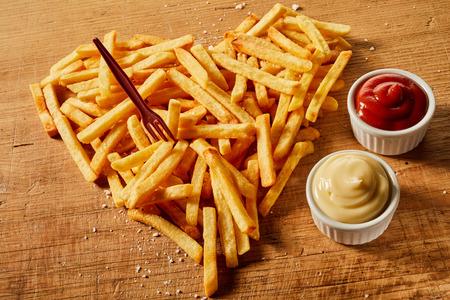 Gesalzene und gewürzte herzförmige Portion gebratene Kartoffelchips mit Senf und Ketchup auf Holz mit Plastikgabel Standard-Bild