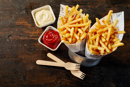 Two takeaway portions of fried potato chips or French fries in paper cones standing in a can with ketchup and mayonnaise on wood