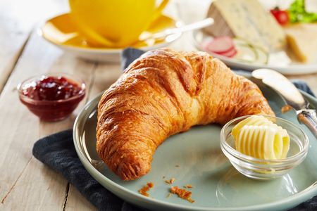 Whole crunchy fresh croissant served on ceramic plate with butter curls in glass bowls. Stock Photo