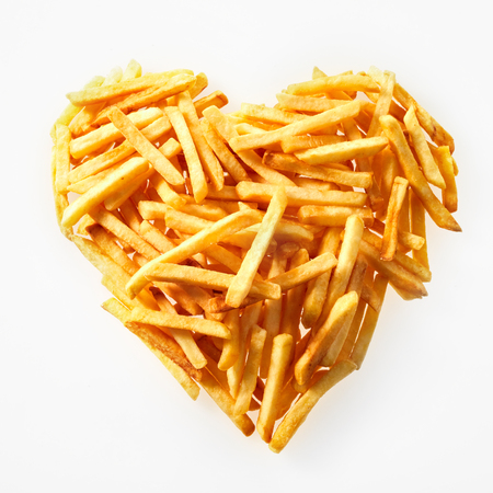 High-angle studio shot close-up of a portion of salty French fries in heart shape on white background for copy space Stok Fotoğraf