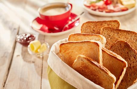 Toast croccanti appena fatti, serviti in un sacchetto di tessuto con caffè e burro sfocati sullo sfondo su un tavolo di legno
