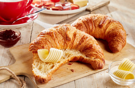 Sliced fresh baked croissant served with butter curls on wooden cutting board