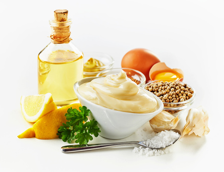 Ingredients for making creamy mayonnaise with fresh lemon, egg yolks, mustard, oil, garlic and salt over a white background
