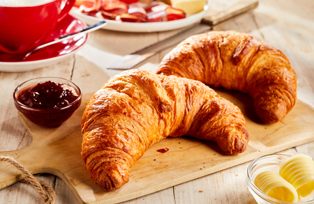 Two fresh baked croissants on wooden cutting board, served with jam and butter in small glass bowls