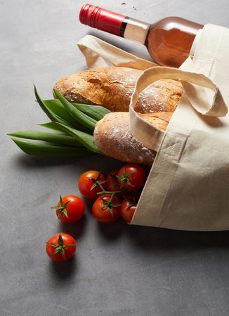 Textile reusable carrier bag with grocery shopping lying on a slate background