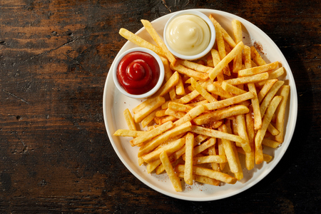 Plate of french fries potatoes served with ketchup and mayonnaise sauces in small bowls, viewed from above on dark wooden background with copy space 版權商用圖片