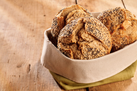 Fabric bag of fresh baked buns of dark wholewheat crunchy bread with seeds, viewed in closeup on wooden table surface with copy space