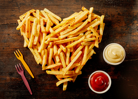 Heart shaped serving of French Fries with dips, dressings or sauce in small bowls alongside on wood Banco de Imagens