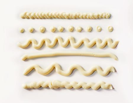 Decorative wavy lines and dots of mayonnaise piped from a tube on a white background for food styling elements