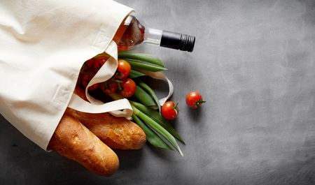 Eco-friendly reusable textile bag with groceries and wine spilling out onto a slate background with copy space Foto de archivo