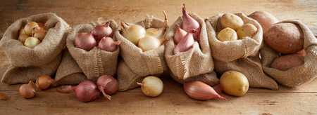 Row of open sacks with different kinds of onion and fresh potatoes on wooden floor background