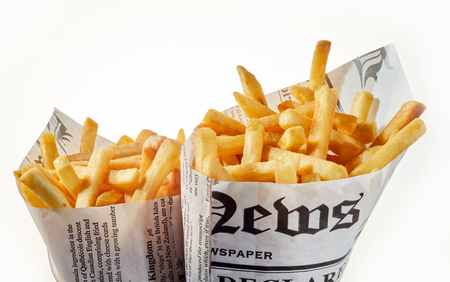 Two newspaper cones of French fries isolated on white in a fast food and takeaway concept