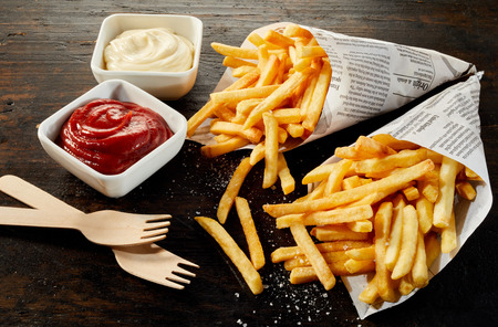 Takeaway servings of deep-fried potato chips or French fries in paper cones with bowls of mayonnaise and ketchup