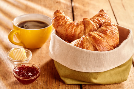Freshly baked flaky croissants served in fabric bag with butter curls, jam and cup of coffee on rustic wooden table 스톡 콘텐츠