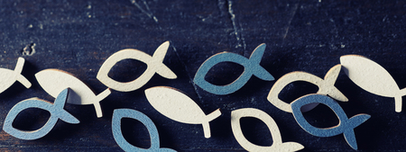 Blue and white cut out Christian religion fish symbols in a row on dark blue background