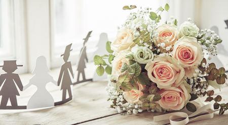 Braut und Bräutigam schneiden Formdekorationen und einen schönen Brautstrauß aus blassrosa Rosen aus, auf der Holzoberfläche der Fensterbank