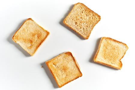 Ensemble de quatre tranches de pain grillé frites isolées sur fond blanc avec ombre, vue d'en haut