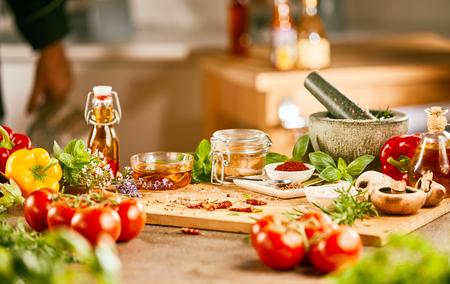 Świeże składniki sałatki z ziołami, przyprawami i oliwą z oliwek oraz kamienny tłuczek i moździerz na drewnianej desce do krojenia w kuchni