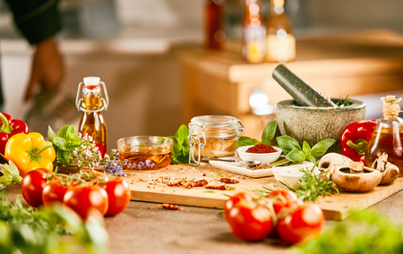 Fresh salad ingredients with herbs, spices, and olive oil and a stone pestle and mortar on a wooden cutting board in a kitchen
