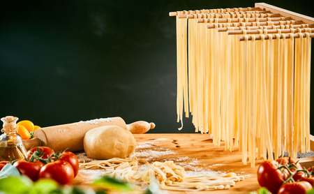 Homemade spaghetti noodles hanging up to dry with fresh ingredients for Italian cuisine on the kitchen table Stock fotó