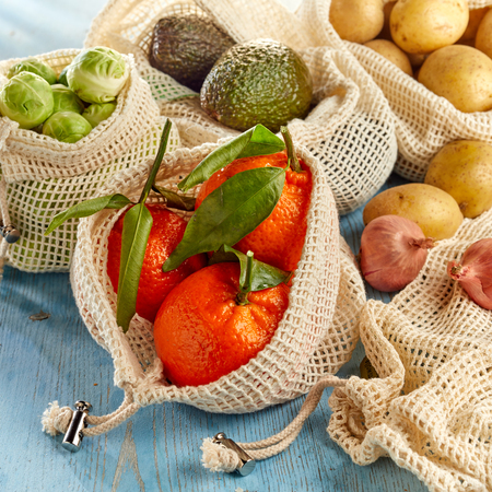 Fresh fruits and organic vegetables from local market packed in eco-friendly reusable net bags, viewed in close-up on wooden surface